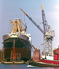 Tug Sea Hound passing by unknown ship in drydock